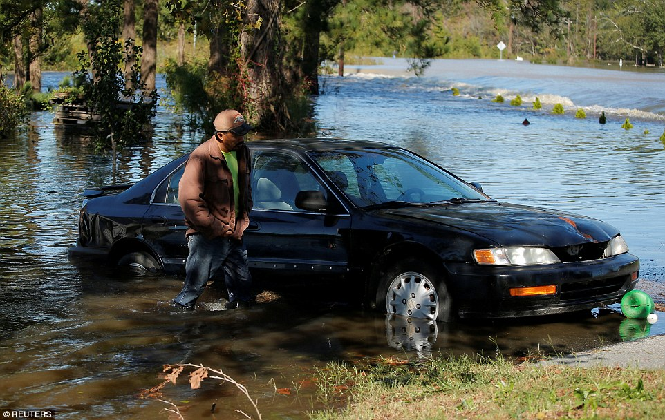 A man walks through the flooded waters to his home in Lumberton on Sunday morning