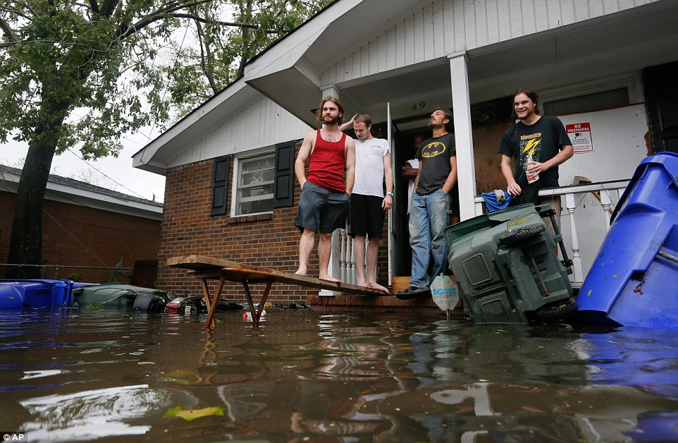 Four Charleston residents stand on their porch and survey Matthew's damage on Saturday afternoon