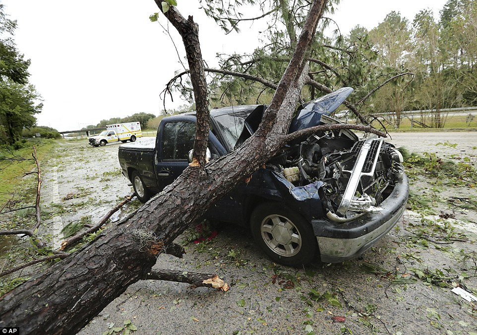 An ambulance responding to a call passes by a truck damaged by a fallen tree on Interstate 16 West in Savannah