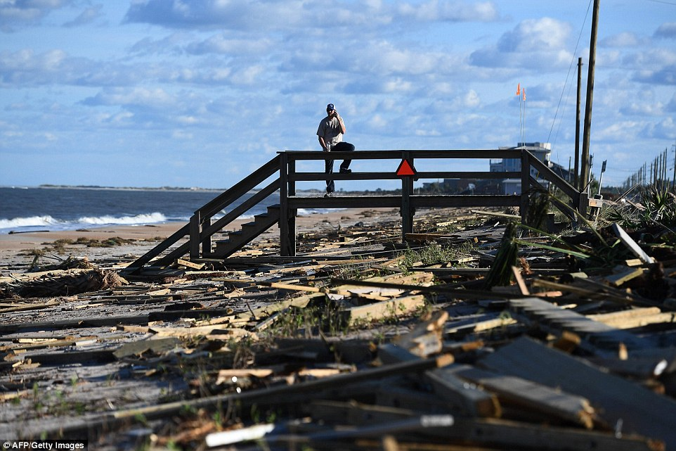A man leans on a damaged boardwalk at a debris covered beach in St Augustine, Florida on Saturday