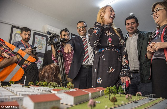 All smiles: Lindsay shared a joke with officials and aid workers as she was shown a model map of the container town