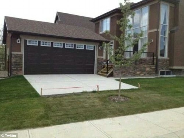 A home owner appears to have built a garage with a white concrete driveway but a tree obstructs the car's path toward the road and has meant the driveway does not meet the gutter