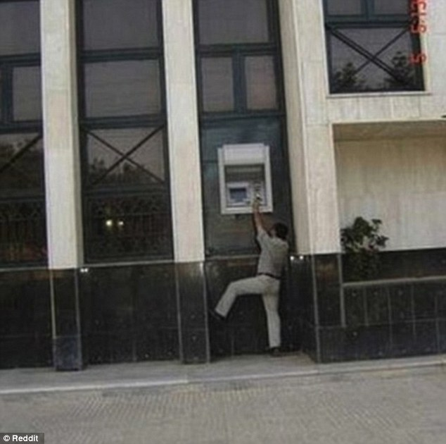 A man reaches up to an unusually high ATM as he tries in vain to withdraw some cash