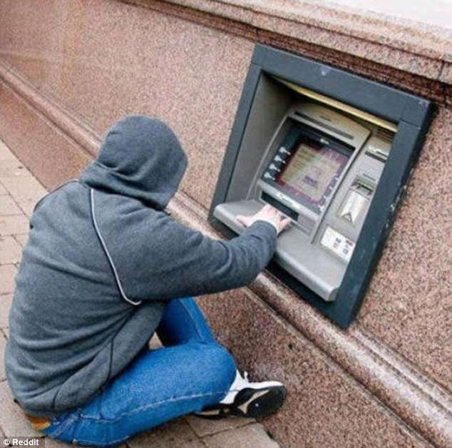 Another man sits on the ground with his legs crossed to be able to use a strangely low ATM