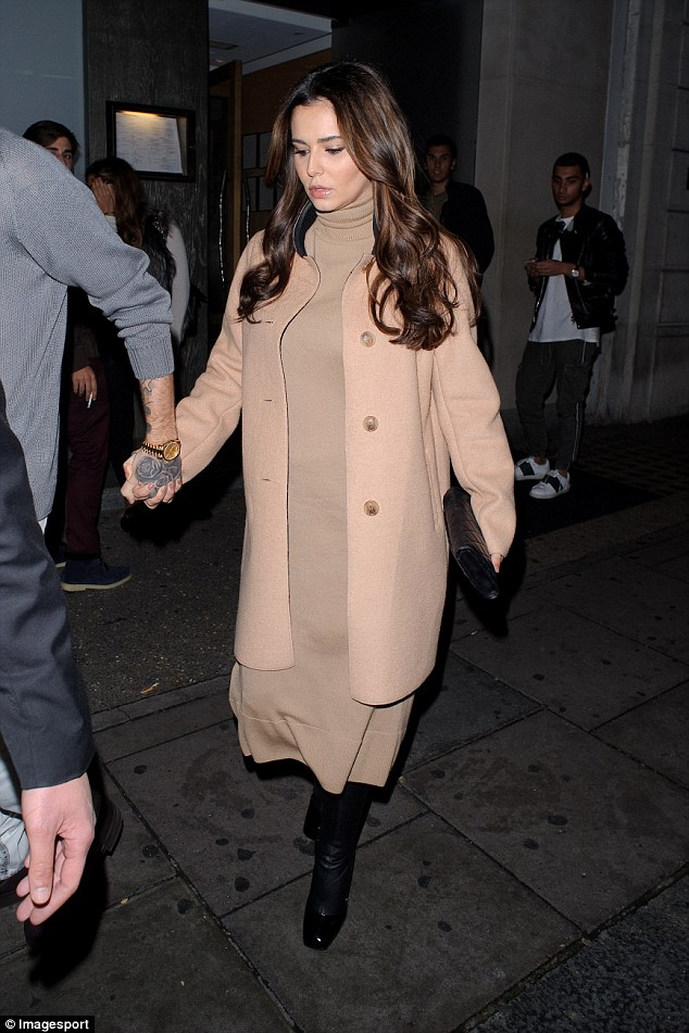 Showing his support: Liam gripped tightly to Cheryl's hand on their exit