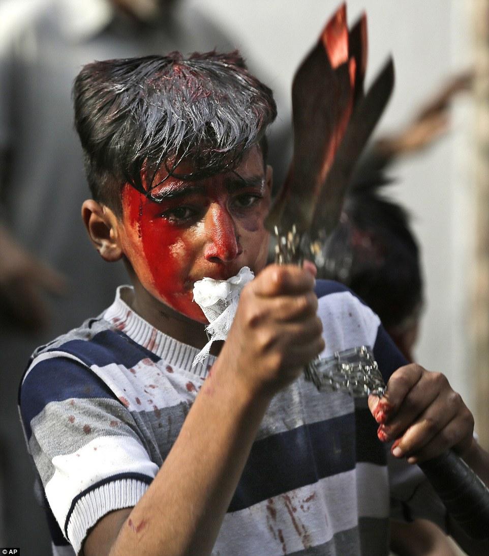 A Kashmiri Shia Muslim boy flagellates himself during a Muharram procession in Srinagar in Indian controlled Kashmir
