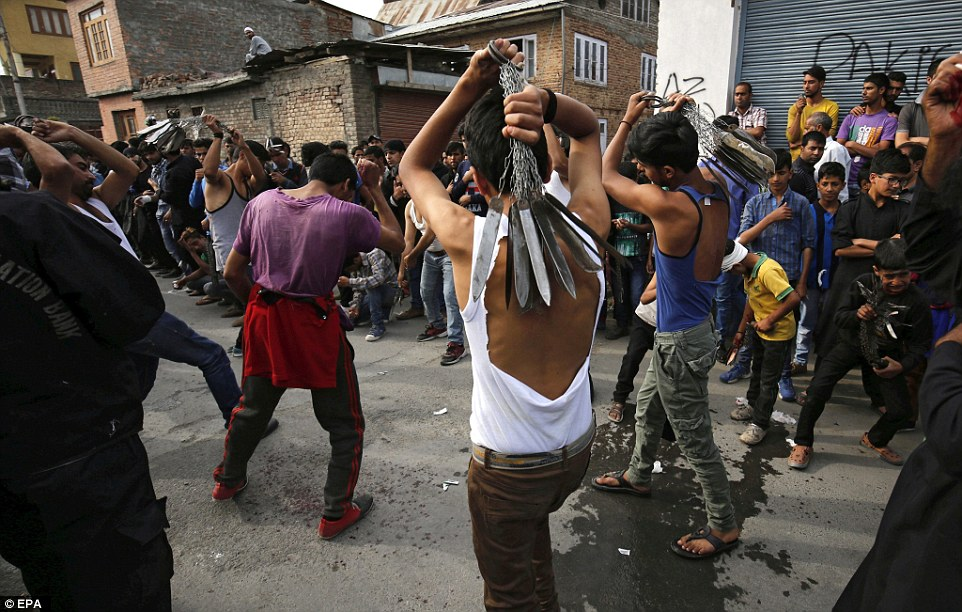 Crowds of people watch the Kashmiri Shia Muslimscarry out the ritual in the streets ofSrinagar, India