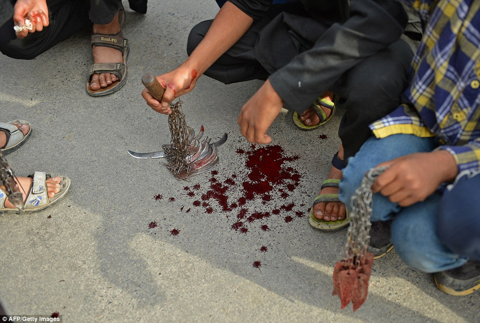 After the ritual in Srinagar, men crouched down to display the blood on the knives they had used to cut themselves