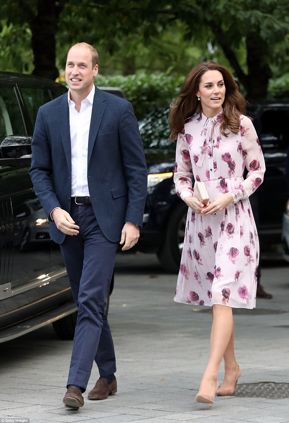 William opted for a smart casual look in navy trousers and a blazer with a white open neck shirt and brown suede loafers