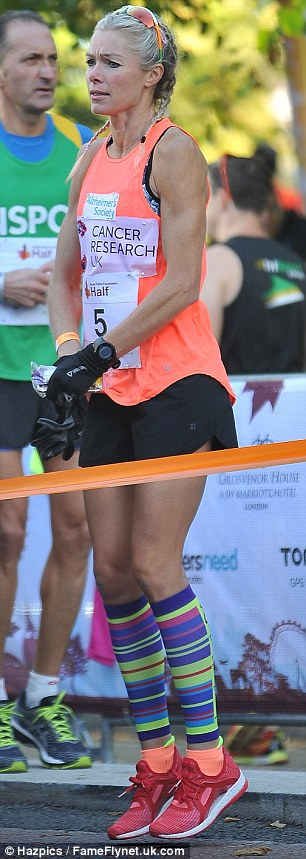 Jog on! Nell's barely there running attire did little to combat the October chill as she jogged on the spot to warm-up before the race