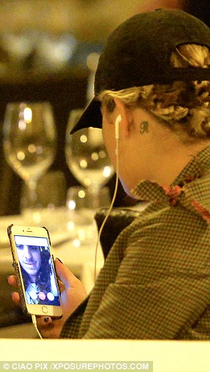 Chatting away: She starred at her screen during dinner