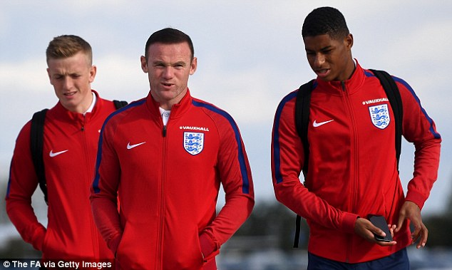 Rooney (centre) will not start when England take on Slovenia on Tuesday evening