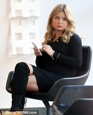 Chilling out: The former Miss GB slipped into her sexy black boots which ruched around her slender legs and flashed a touch of skin whilst holding onto her phone