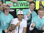 World champion Mercedes driver Lewis Hamilton of Britain, second placed, and his teammate winner Nico Rosberg of Germany celebrates with team members after the Emirates Formula One Grand Prix at the Yas Marina racetrack in Abu Dhabi, United Arab Emirates, Sunday, Nov. 29, 2015. Nico Rosberg completed a hat trick of victories to end the Formula One season when he won the Abu Dhabi Grand Prix on Sunday, profiting from a questionable tire strategy by his Mercedes teammate Lewis Hamilton.  Mercedes driver Nico Rosberg of Germany won the race. (AP Photo/Kamran Jebreili)