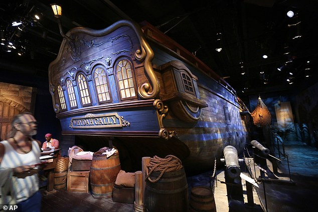 A museum visitor, left, walks past a life-size replica of the hull of the pirate ship at the Whydah Pirate Museum, in Yarmouth, Massachusetts