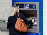 Woman at the cash machine of the Royal Bank of Scotland, RBS, in London, England, United Kingdom, Europe