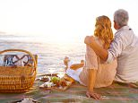 Romantic senior couple seated on the beach and looking away during a picnic