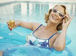 Senior woman relaxing on float in swimming pool, portrait MIDDLE AGED WOMAN IN A SWIMMING POOL HOLDING A DRINK WEARING SWIMSUIT AND SUNGLASSES WOAM RELAXING IN POOL