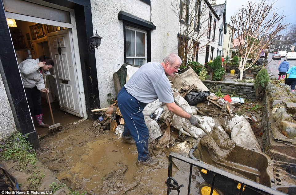 Clean-up: Thousands of families are  facing the 'soul-destroying' prospect of eight months away from their homes as insurers prepare for payouts of £500million in the aftermath of Storm Desmond. A resident in Keswick is pictured clearing debris from his flooded home
