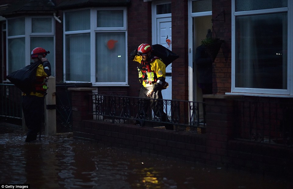 Rescue teams continue to help evacuate people from their severely flooded homes as dusk falls in Carlisle, Cumbria, this evening