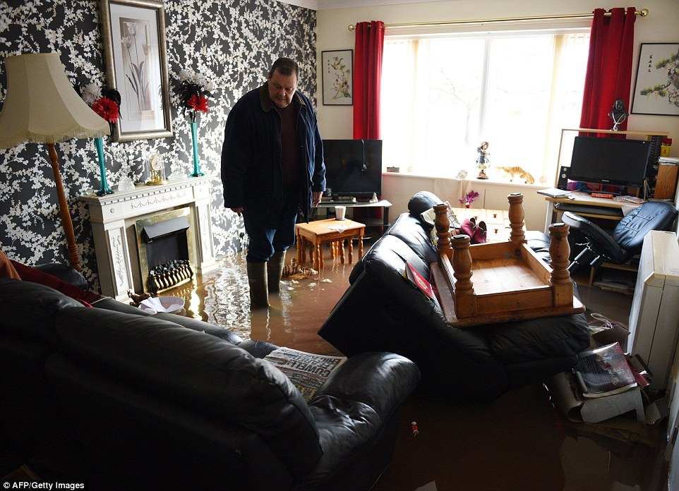 Brian McCann surveys the damage as he stands in floodwater in his living room in Carlisle following a weekend of heavy rain in Cumbria