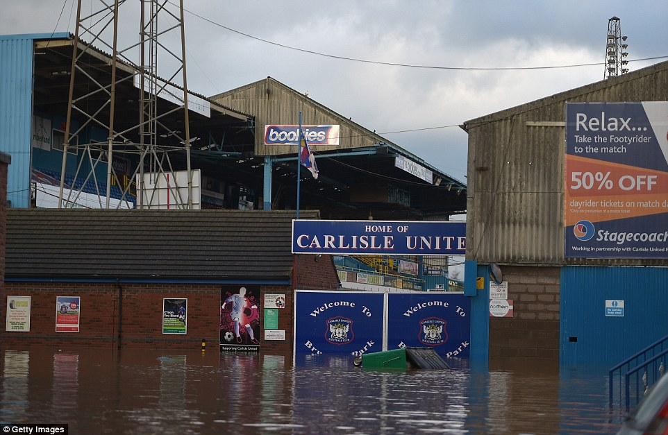 Ground workers at Carlisle United have a huge job on their hands to pump out the floodwater and return the pitch to a playable state