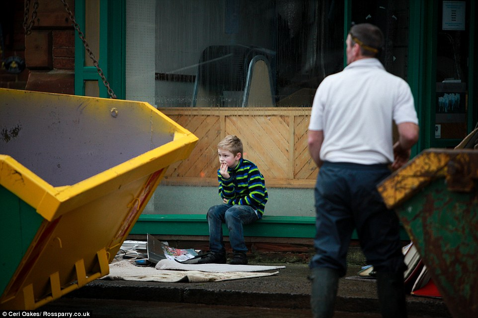 The youngster is pictured watching on as skips are delivered outside his father's business, which was severely flooded at the weekend