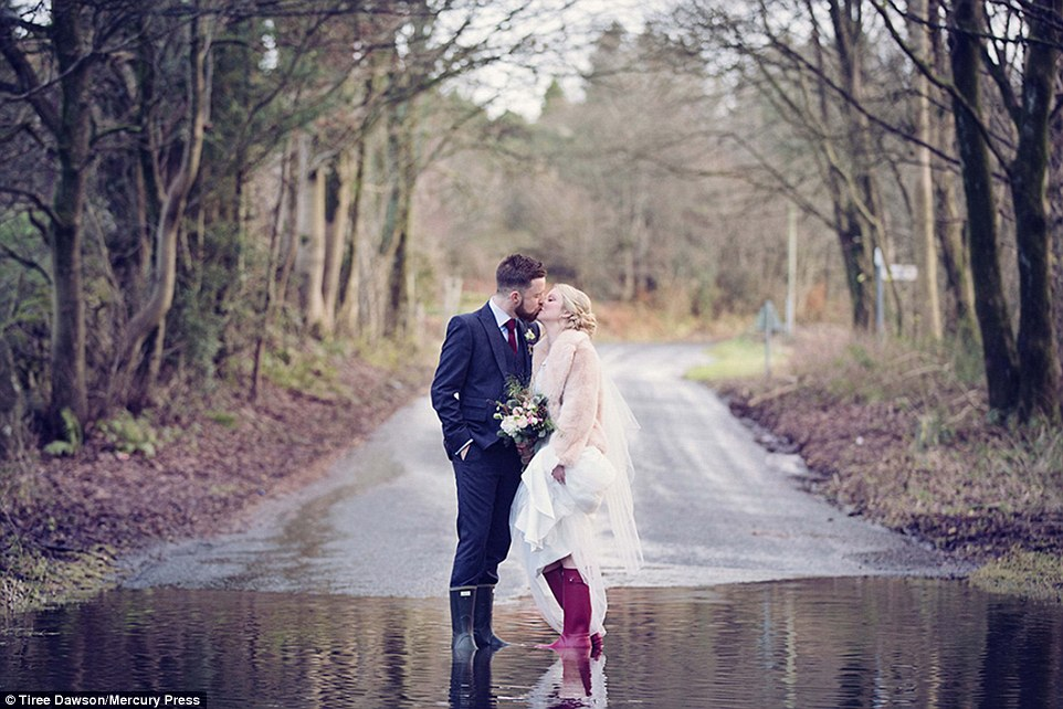 Hayley Caunce, 29, and Jamie Traynor, 31, didn't let the wet weather and severe flooding ruin their wedding day near Kendal, Cumbria, on Sunday. They posed in their wellies in a flooded road after exchanging their vows at The Wild Boar in Crook as Storm Desmond swept in