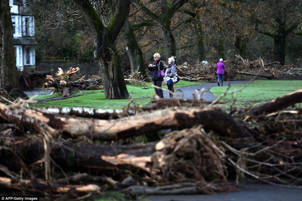 Shock: People walk along the bank of the River Greta in Keswick as they survey the debris left following extensive flooding in the town