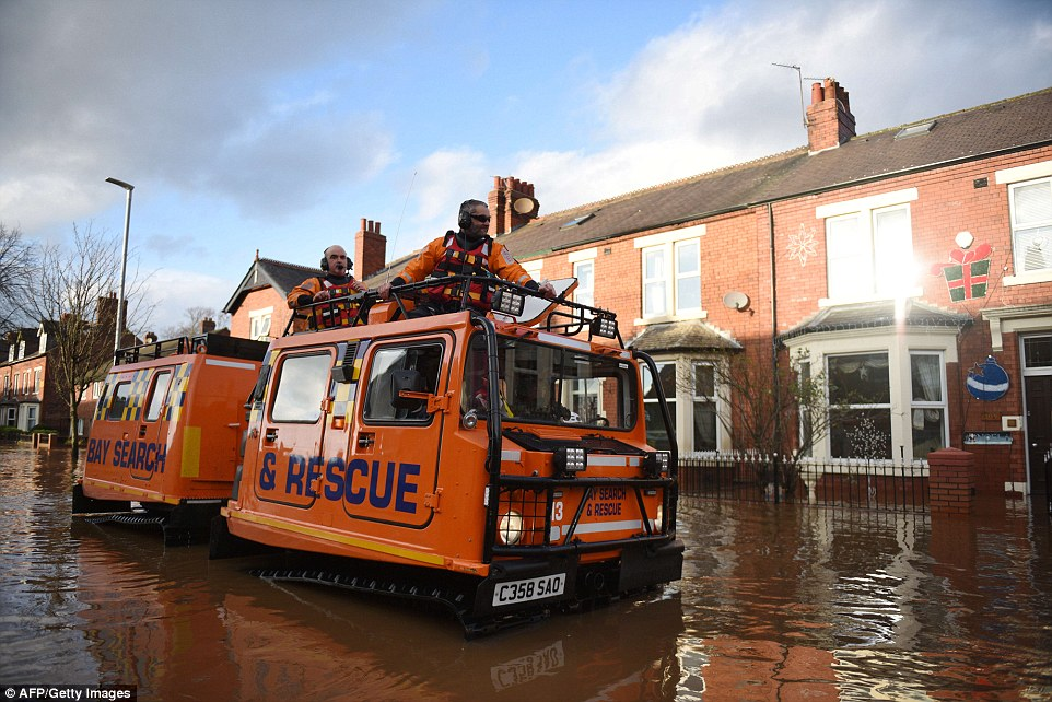 Members of the emergency services travel in an amphibious vehicle as they prepare to rescue residents from their homes in Carlisle
