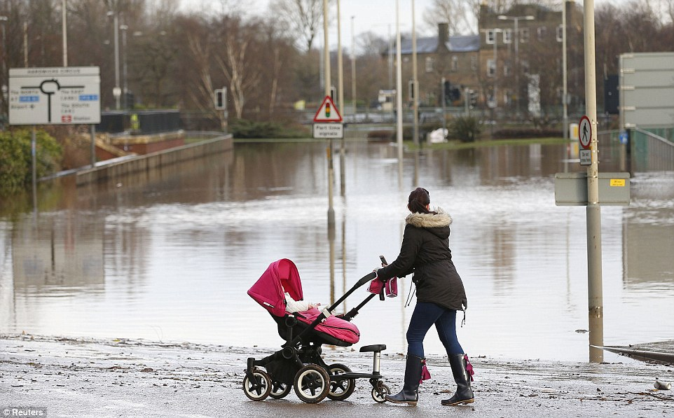 A woman with a pushchair stops to look at the city centre submerged under flood waters in Carlisle, north west England on Monday