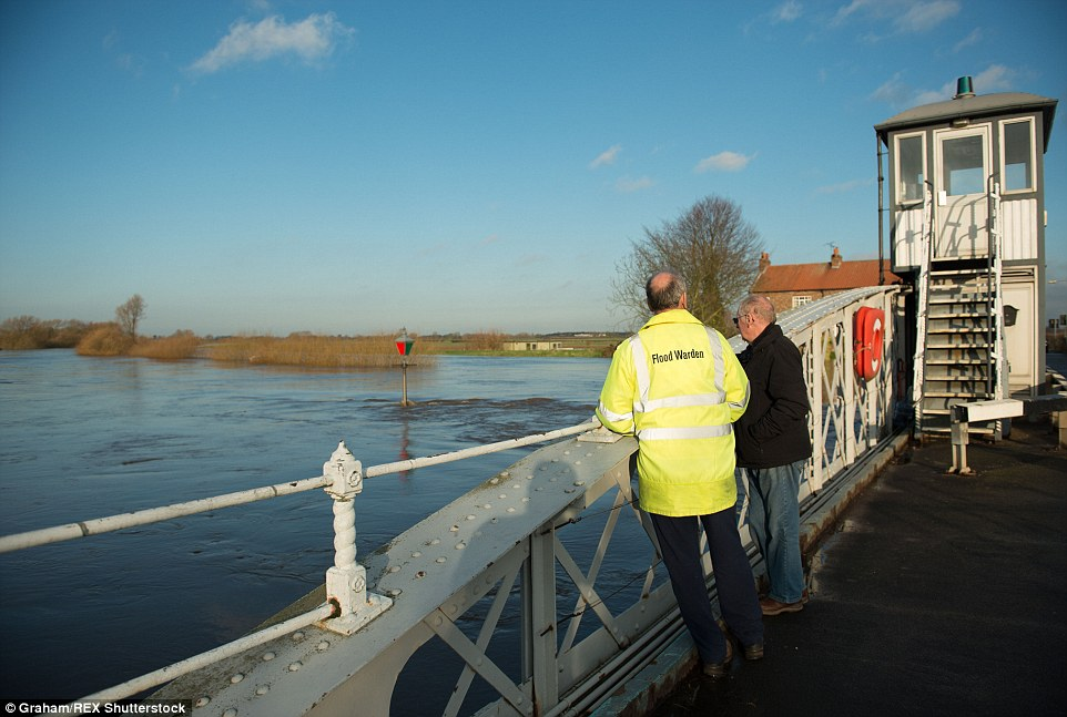 A flood warden for Cawood is seen looking at the River Ouse in Yorkshire, which burst its banks over the weekend following heavy rain