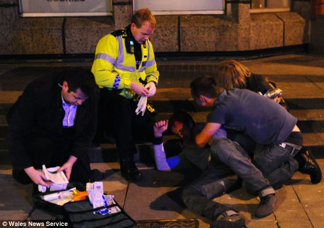 Wounded: A young man is treated following a night out in the centre of Cardiff as friends lend their support