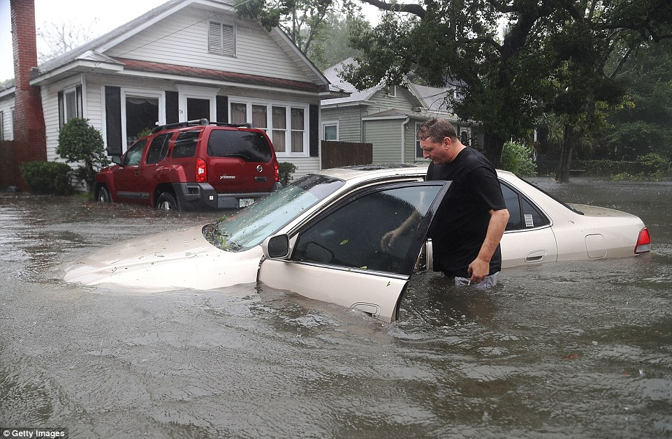 Not going anywhere: Rob Birch checks on his car which floated out of his drive way as Hurrican Matthew passes through the are in St Augustine; the area has been particularly badly hit by flooding