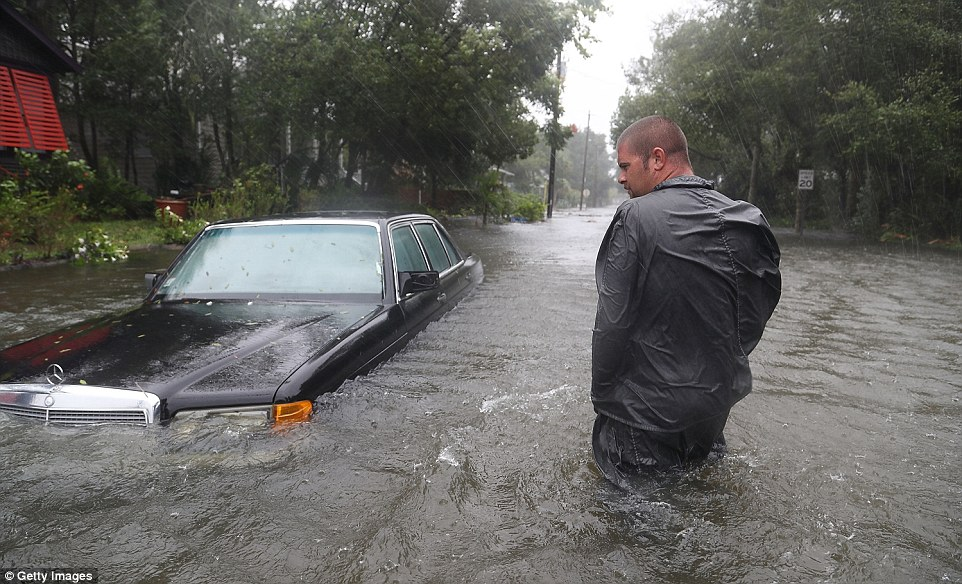 Devastated: Nick Lomasney walks through heavy wind and a flooded street in St Augustine; Florida, Georgia and the Carolinas have all declared a state of emergency in preparation for Matthew