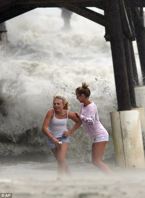 Kaleigh Black, 14, left, and Amber Olsen, 12, run for cover as they are pelted with waves at the Cocoa Beach Pier