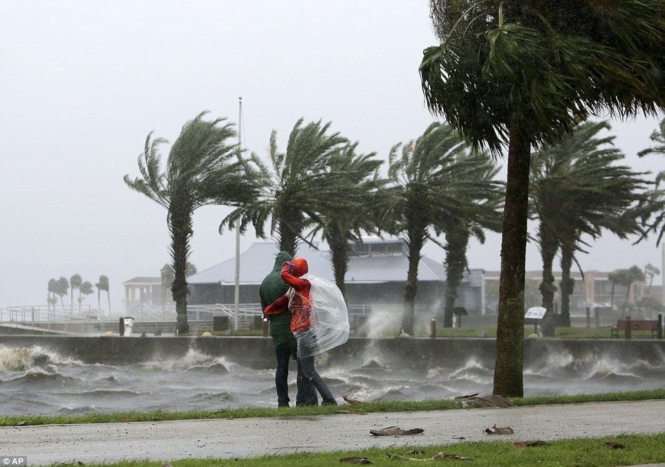 Romantic stroll: A couple walk along the Sanford Riverwalk along Lake Monroe as strong winds and rain continue to lash downtown Sanford, Florida; authorities have warned the danger is far from over