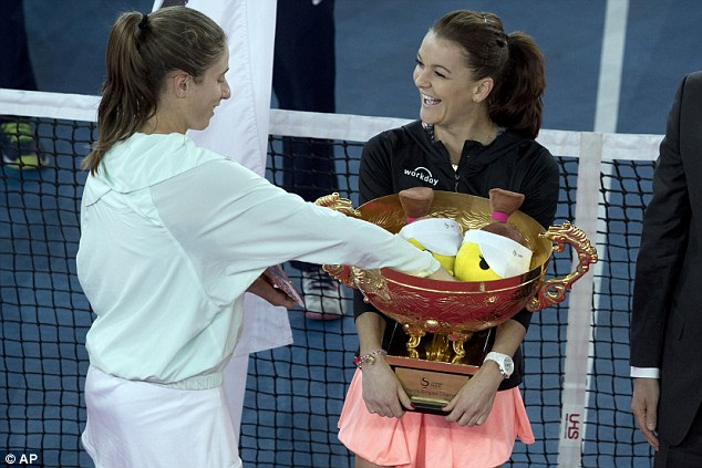 Konta shares a joke with her opponent by placing a mascot inside her trophy after the match