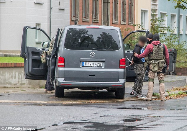 A man is taken to a vehicle. German police say two people have been arrested but haven't confirmed who they are