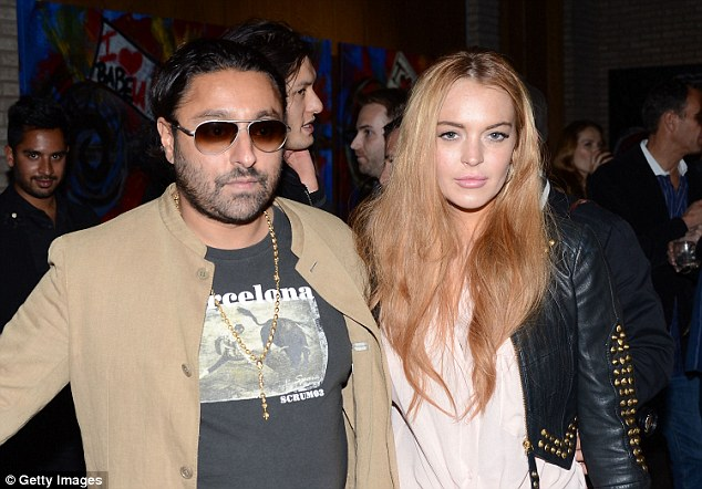 Party guy: Vikram Chatwal, long-time friend of Lindsay Lohan (both pictured in one of his hotels), is accused of attacking two dogs with an aerosol can and a lighter Friday