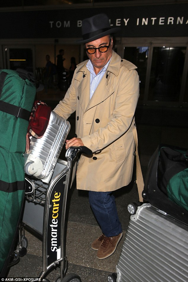 Heavy load: Sporting a clean-shaven style, the silver fox pushed an enormous green bag of golf clubs with his initials engraved on the side
