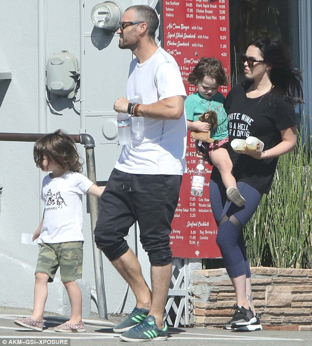 Family first: Megan revealed her fit form in sheer paneled navy cropped leggings; pictured with Brian and sons Noah (l) and Bodhi (r)