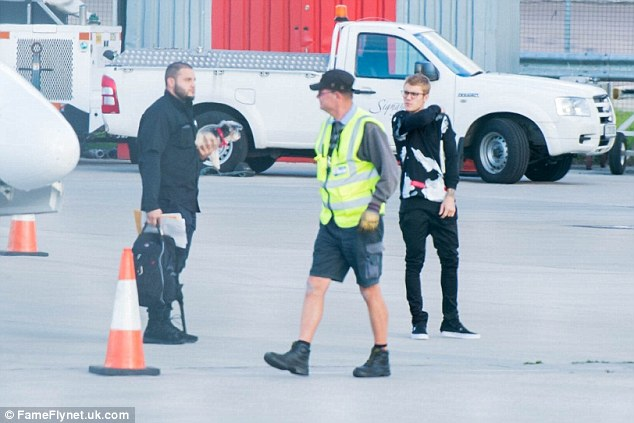 Upstaged: Justin's low-key outfit was outdone by one airport staff member who rocked the short shorts and boots combo, complete with baseball cap, gloves and a high vis jacket