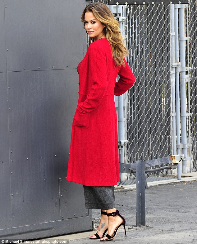 Smoldering gaze:Brooke wowed in a tailored red trench coat with a matching colored blouse