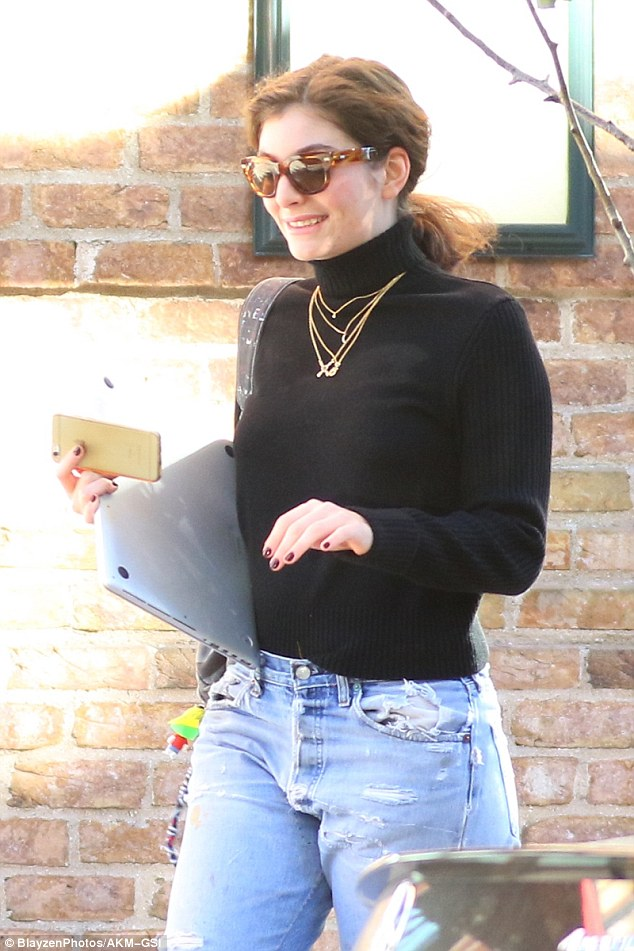 Stylish: The Royals hitmaker sported blue boyfriend jeans and a black turtle neck sweater, while clutching a laptop and a cell phone