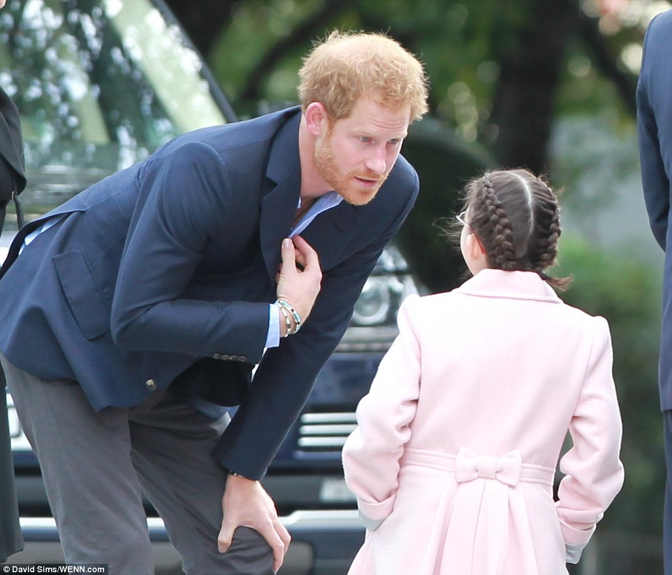 Prince Harry leans over to chat to Joanne Sibley who was chosen to greet the royals as they arrived at London's County Hall