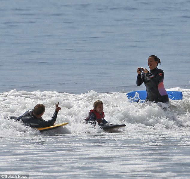 Silly in the surf: As the precious family splashed around on their colorful boards, Alanis snapped some pictures while nearly getting knocked over by the waves