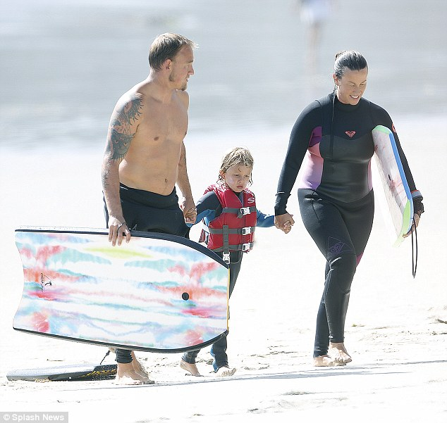 Beach day! The mother-of-two sported a long-sleeved pink and black wet suit nearly three months after giving birth to her baby girl. Her beau and little boy also donned similar suits
