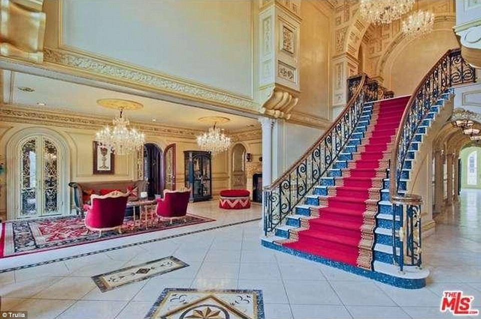 One of the home's grand staircases is seen above, draped in a red carpet for the next owner