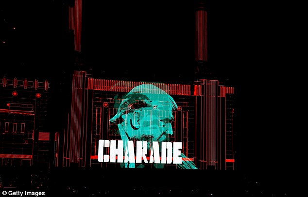During the set, other images of Trump flashed on stage. One showed an image of the GOP nominee with the words 'CHARADE' written on it